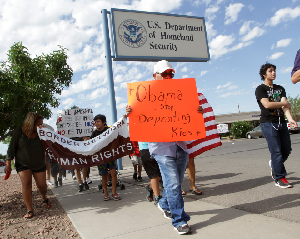 Photo - Marchers held signs as they made their way to Department of Homeland Security offices, protesting immigration policies Thursday, July 10, 2014, in El Paso, Texas. (AP Photo/El Paso Times, Victor Calzada)