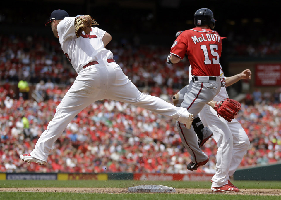 Photo - Washington Nationals' Nate McLouth (15) is safe at first as St. Louis Cardinals first baseman Matt Adams, left, leaps out of the way of McLouth during the fifth inning of a baseball game on Sunday, June 15, 2014, in St. Louis. (AP Photo/Jeff Roberson)