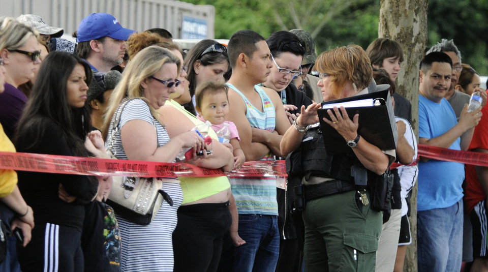 Photo - A police officer explains to parents how they are to be reunited as students arrive by bus at a shopping center parking lot in Wood Village, Ore., after a shooting at Reynolds High School Tuesday, June 10, 2014, in nearby Troutdale. A gunman killed a student at the high school east of Portland Tuesday and the shooter is also dead, police said.(AP Photo/Greg Wahl-Stephens)