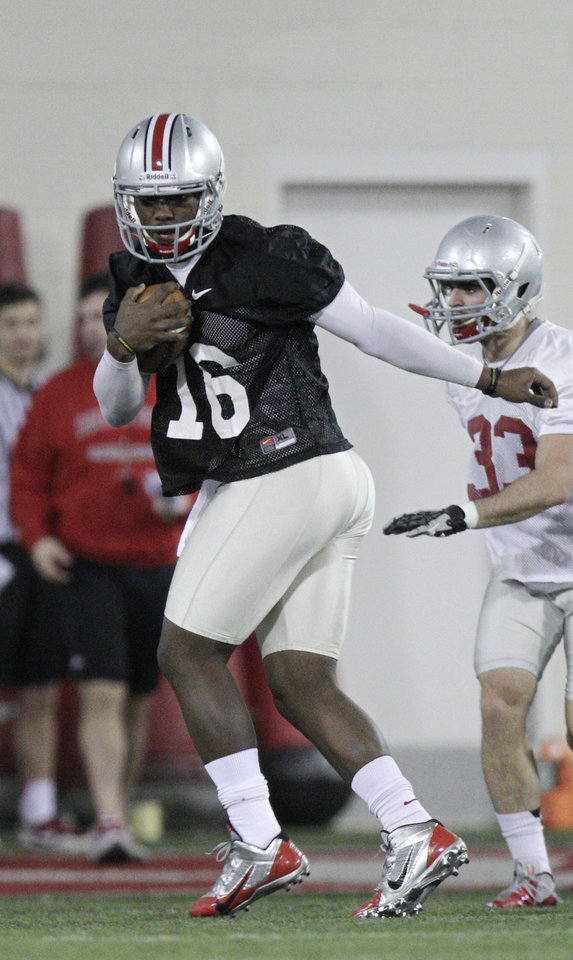 Photo - Ohio State quarterback JT Barrett warms up during their Spring NCAA college football practice Tuesday, March 4, 2014, in Columbus, Ohio. (AP Photo/Jay LaPrete)