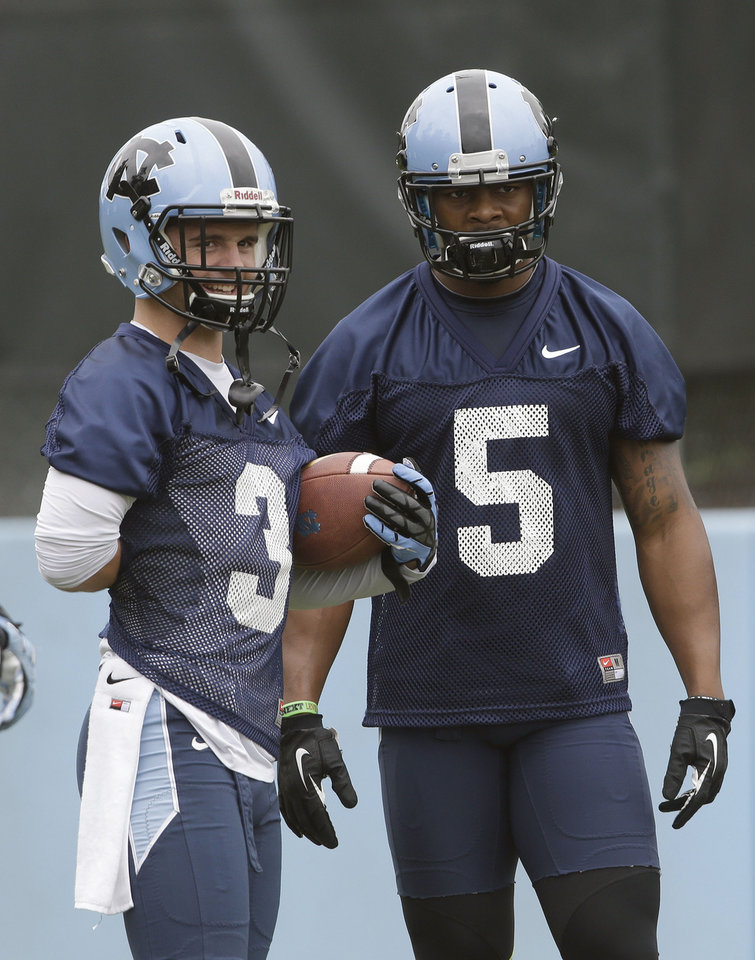 Photo - In this photo taken Friday, Aug. 1, 2014,  North Carolina wide receivers Ryan Switzer (3) and T.J. Thorpe (5) pause during a break an NCAA football practice in Chapel Hill, N.C.  (AP Photo/Gerry Broome)