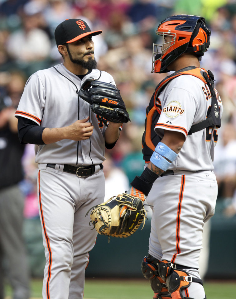 Photo -   San Francisco Giants relief pitcher Sergio Romo, left, meets with catcher Hector Sanchez before getting pulled during the ninth inning of a baseball game against the Seattle Mariners at Safeco Field in Seattle, Sunday, June 17, 2012. The Mariners won 2-1. (AP Photo/Stephen Brashear)