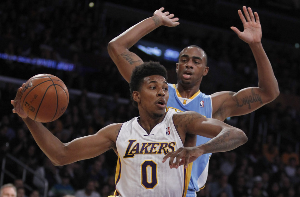 Photo - Los Angeles Lakers forward Nick Young (0) drives inside of Denver Nuggets forward Darrell Arthur, right, to make a pass during the first half of an NBA basketball game, Sunday, Jan. 5, 2014, in Los Angeles. (AP Photo/Alex Gallardo)