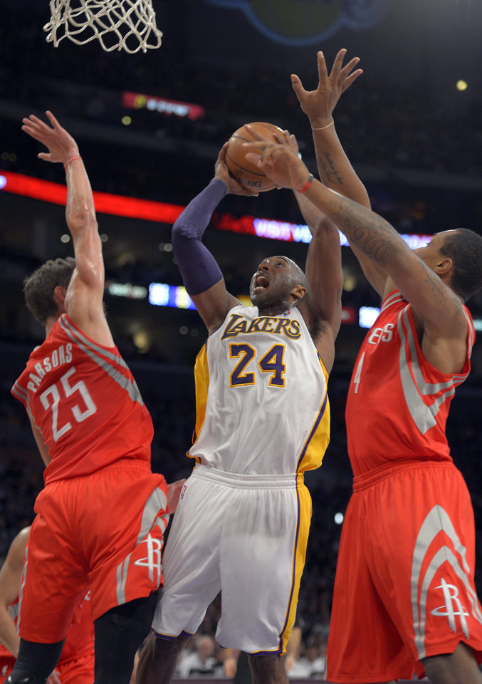 Los Angeles Lakers guard Kobe Bryant, center, puts up a shot as Houston Rockets forward Chandler Parsons, left, and forward Greg Smith defend during the first half of their NBA basketball game, Sunday, Nov. 18, 2012, in Los Angeles. (AP Photo/Mark J. Terrill)
