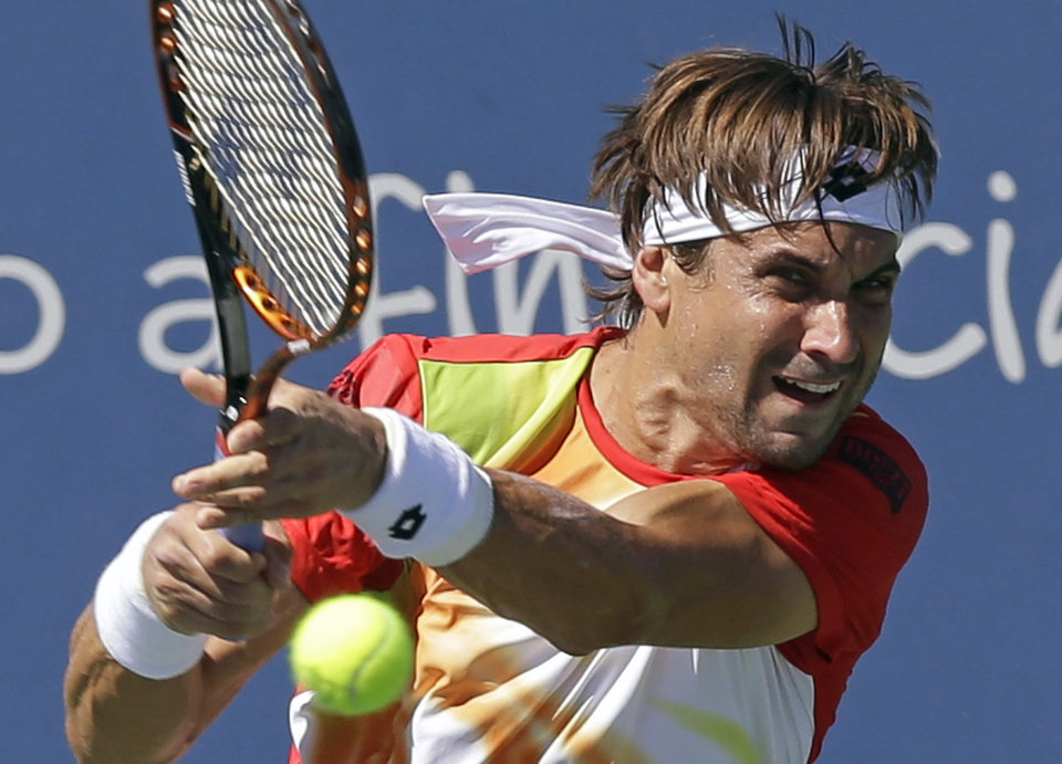 Photo - David Ferrer, from Spain, hits a backhand against Tommy Robredo, from Spain, during a match at the Western & Southern Open tennis tournament, Friday, Aug. 15, 2014, in Mason, Ohio. (AP Photo/Al Behrman)