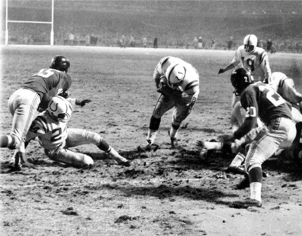 Photo - NFL FOOTBALL / CHAMPIONSHIP: ** ADVANCE FOR WEEKEND EDITIONS, AUG. 30-31 ** FILE ** In this Dec. 28, 1959, file photo, Baltimore Colts fullback Alan Ameche advances through a big opening provided by teammates to score the winning touchdown in overtime period against the New York Giants at Yankee Stadium in New York, Dec. 28, 1958.  Colts' Lenny Moore gets a good block on Giants' Emlen Tunnell (45) at left.  Colts quarterback Johnny Unitas (19) is at right along with Giants' Jim Patton (20).  Batimore won, 23-17, for National Football League title in the first overtime finish in title history.  (AP Photo) ORG XMIT: NY177