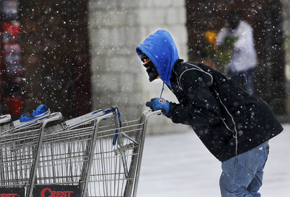 Photo - A worker returns empty shopping carts to the front of Crest Foods in Midwest City. Snow began falling in central Oklahoma around 7 Sunday morning, Feb. 2, 2014.   Photo by Jim Beckel, The Oklahoman