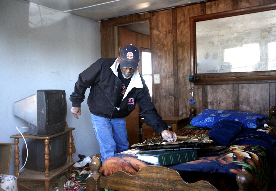 Photo - Israel Sanchez salvages items in his brother-in-laws home at the Hideaway mobile home park, Sunday, April 15, 2012.  A tornado struck Woodward early Sunday morning. Photo by Sarah Phipps, The Oklahoman.