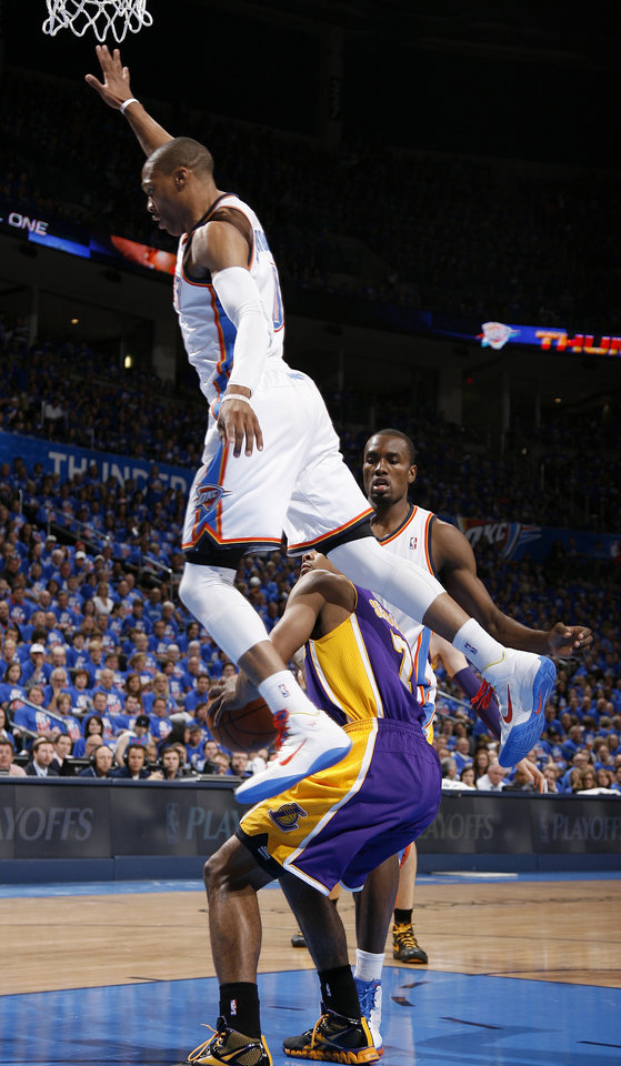 Photo - Oklahoma City's Russell Westbrook (0) leaps past Los Angeles' Ramon Sessions (7) as Oklahoma City's Serge Ibaka (9) watches during Game 5 in the second round of the NBA playoffs between the Oklahoma City Thunder and the L.A. Lakers at Chesapeake Energy Arena in Oklahoma City, Monday, May 21, 2012. Photo by Bryan Terry, The Oklahoman