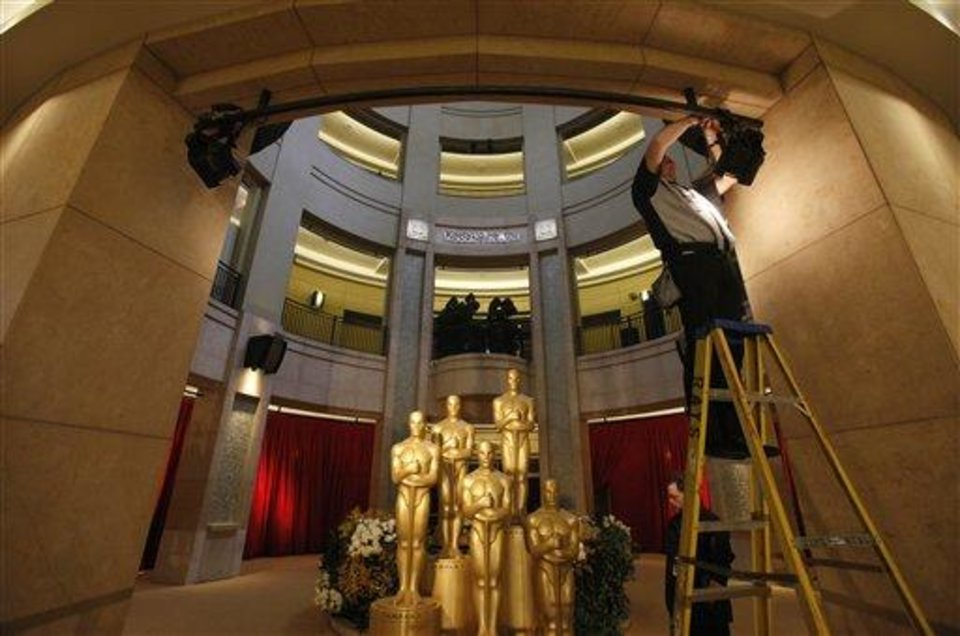 The lights are set to illuminate Oscar statues at the entrance to the Kodak Theatre as preparation continues for the 84th Academy Awards in Los Angeles on Sunday, Feb. 26, 2012.  The Oscars will be held later in the day.