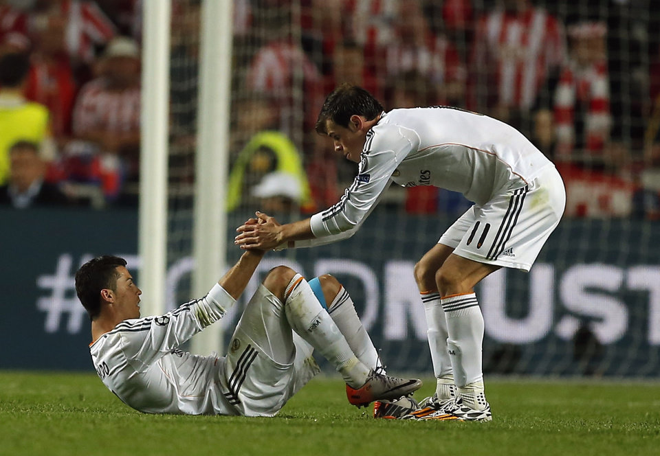Photo - Real's Cristiano Ronaldo, left,  is helped by teammate Gareth Bale, during the Champions League final soccer match between Atletico Madrid and Real Madrid, at the Luz stadium, in Lisbon, Portugal, Saturday, May 24, 2014. (AP Photo/Andres Kudacki)