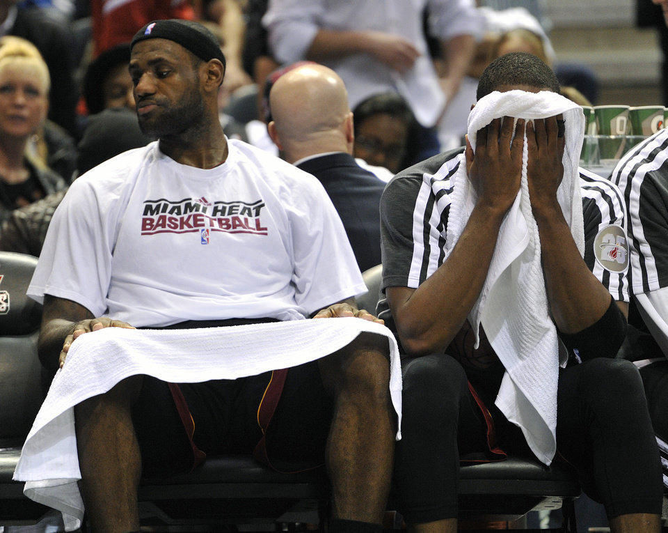 Miami Heat\'s LeBron James, left , and Dwyane Wade sit on the bench in the closing seconds of an NBA basketball game against the Milwaukee Bucks, Saturday, Dec. 29, 2012, in Milwaukee. The Bucks defeated the Heat 104-85. (AP Photo/Jim Prisching)