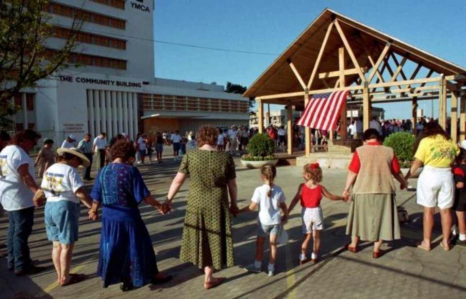 Photo -  People clasp hands around the Heartland Chapel during the July 1995 dedication ceremony for the open-air structure which was built with donations from numerous groups, including Jewish and Muslim faith communities. [The Oklahoman Archives]