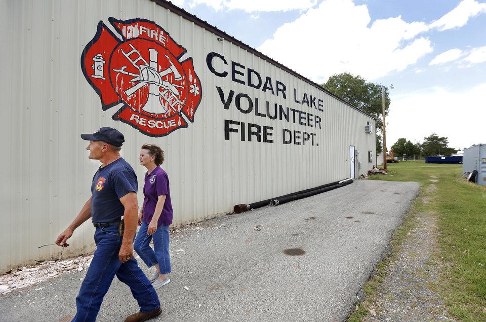 Photo - The future of the Cedar Lake Volunteer Fire Department may now be in dispute because Canadian County has sold the land beneath the fire station. An employee of the county bought the land for $100 after being the only person to bid at auction. Assistant Fire Chief Judy Gipson walks with her husband, Randy, also a firefighter, near the fire department's building east of Hinton.  Jim Beckel -  THE OKLAHOMAN