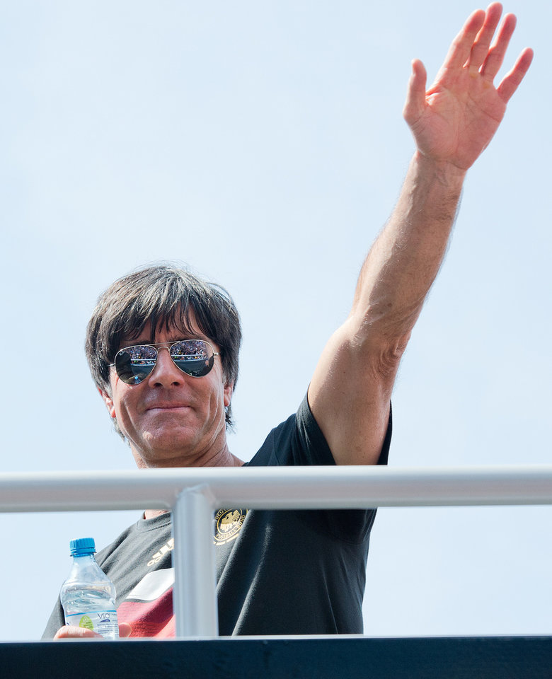 """Photo - German national soccer coach Joachim Loew waves to fans after the arrival of the German soccer squad in Berlin, Tuesday July 15, 2014. Germany's World Cup-winning team has returned home  from Brazil to celebrate the country's fourth title with huge crowds of fans. The team's Boeing 747 touched down at Berlin's Tegel airport midmorning Tuesday after flying a lap of honor over the """"fan mile"""" in front of the landmark Brandenburg Gate.   (AP Photo/dpa Bernd von Jutrczenka)"""