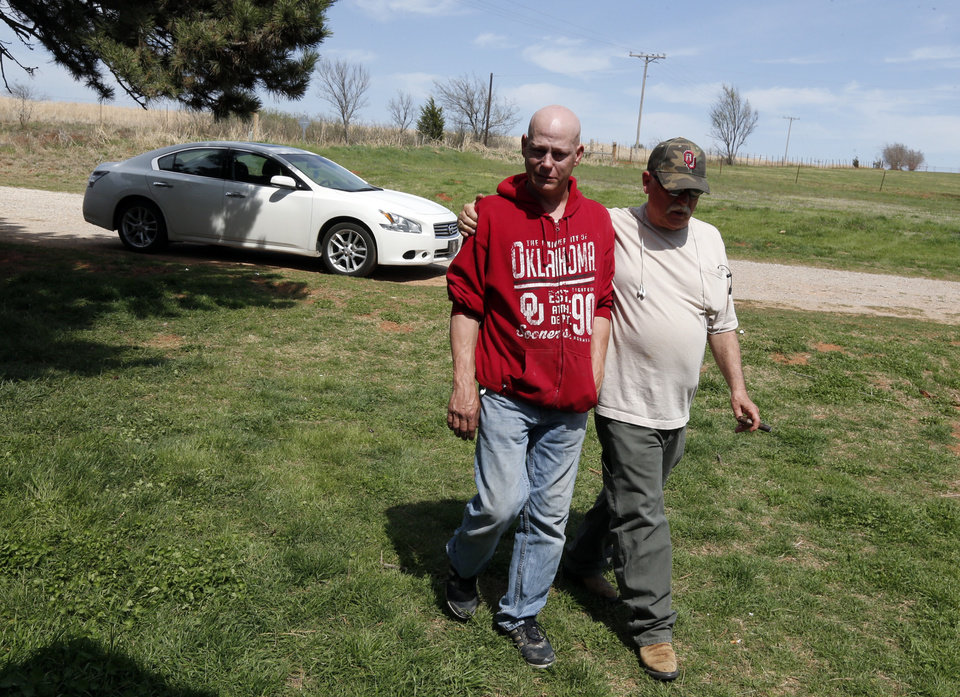 Photo - Clinton Flowers is comforted by his step-father Mike Shannon on Thursday, April 10, 2014 in Cole, Okla.  Flowers found his wife  bound and lifeless at their home on Wednesday.   Photo by Steve Sisney, The Oklahoman