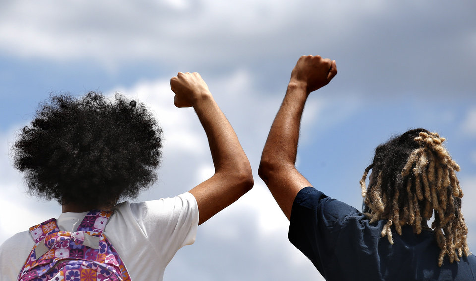 Photo - Protesters hold their fist in the air on the bridge on Main Street over 1-35 in Norman, Okla.  Tuesday, June 2, 2020.  [Sarah Phipps/The Oklahoman]