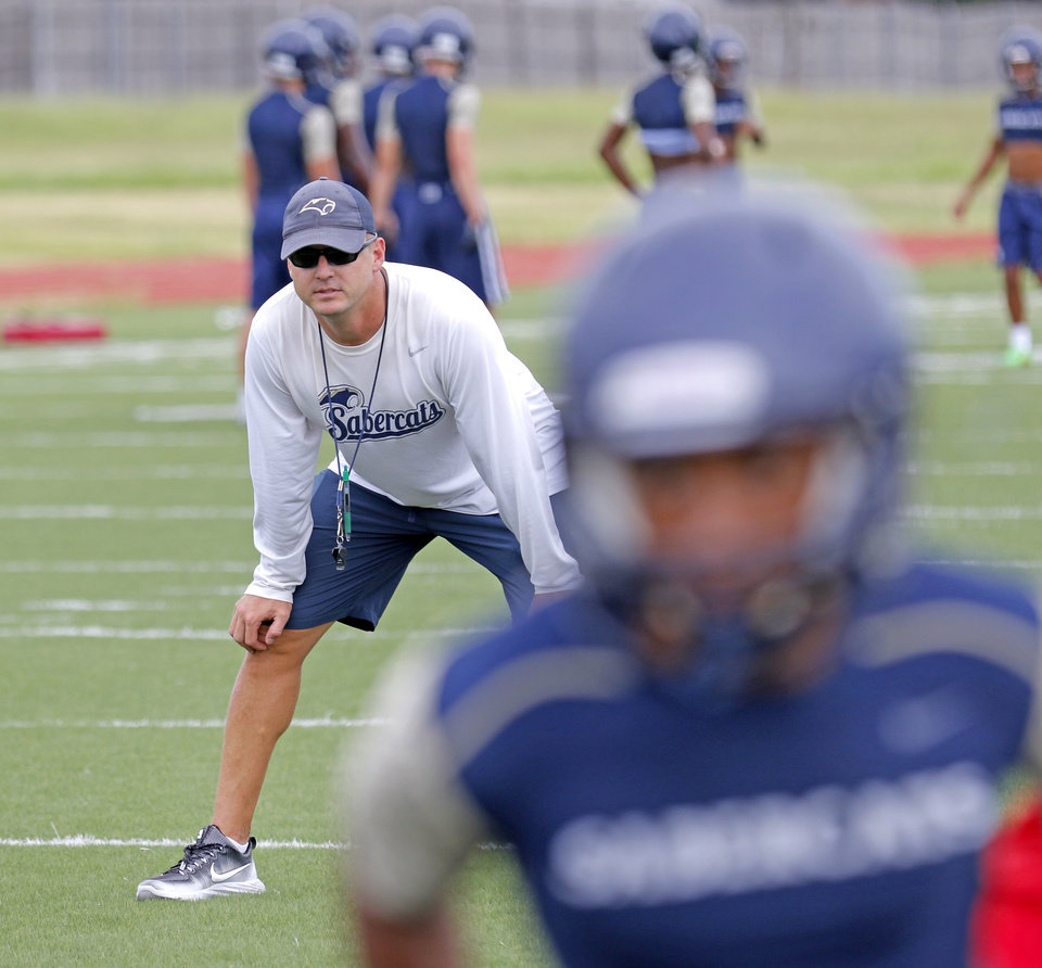 Photo - Southmoore football coach Jeremy Stark watches practice in Moore, Monday August, 8  2016. Photo By Steve Gooch, The Oklahoman