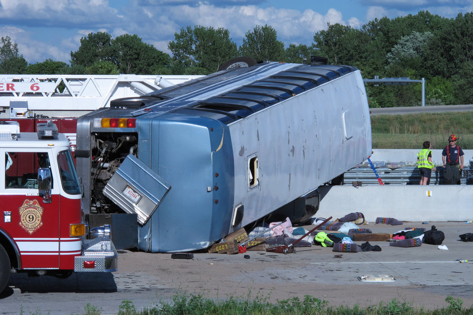 Seat cushions, clothing and other objects line the pavement next to the wreckage of bus that crashed Saturday, July 27, 2013, on Indianapolis' far north side while carrying teenagers returning from a summer camp in Michigan. Three people were killed and 26 others were taken to local hospitals following the crash, which occurred when the bus exited an interstate ramp and crashed into a concrete retaining wall. Investigators don't yet know what caused the crash about a mile from its destination, Colonial Hills Baptist Church.  (AP Photo/Rick Callahan)