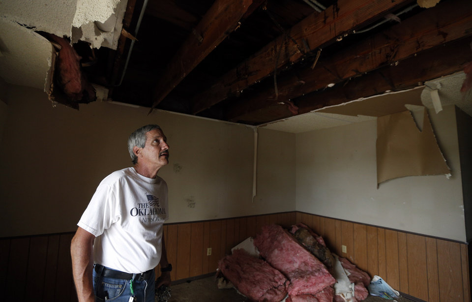 Photo -  Bret Downs looks at the damaged roof of his apartment at Oakwood Apartments, 5824 NW 34. The apartment was damaged by heavy rains Friday morning. PHOTO BY SARAH PHIPPS, THE OKLAHOMAN   SARAH PHIPPS -