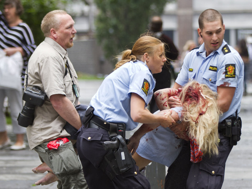 A young victim is helped in the centre of Oslo, Friday July 22, 2011, following an explosion that tore open several buildings including the prime minister's office, shattering windows and covering the street with documents.(AP Photo/Winje