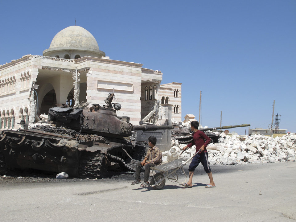 Photo -   Syrian boys fetching water in a wheelbarrow look at a destroyed Syrian tank near a damaged mosque in the city of Azaz, Syria, on Monday, Aug. 20, 2012. (AP Photo/Ben Hubbard)