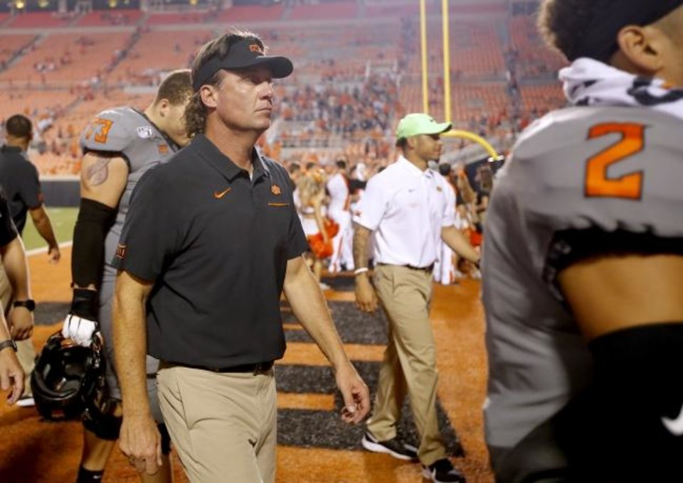 Photo -  Oklahoma State football coach Mike Gundy walks off the field after last season's win against McNeese State at Boone Pickens Stadium in Stillwater. [Sarah Phipps/The Oklahoman]