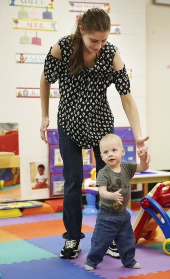 Photo -  Dezirae Berend, a teacher in the infant room, helps Greyson Sawatzky, 11 months, walk recently at Putnam City Smart Start Childcare, an affordable child care facility for Putnam City teachers. [Nate Billings/ The Oklahoman]