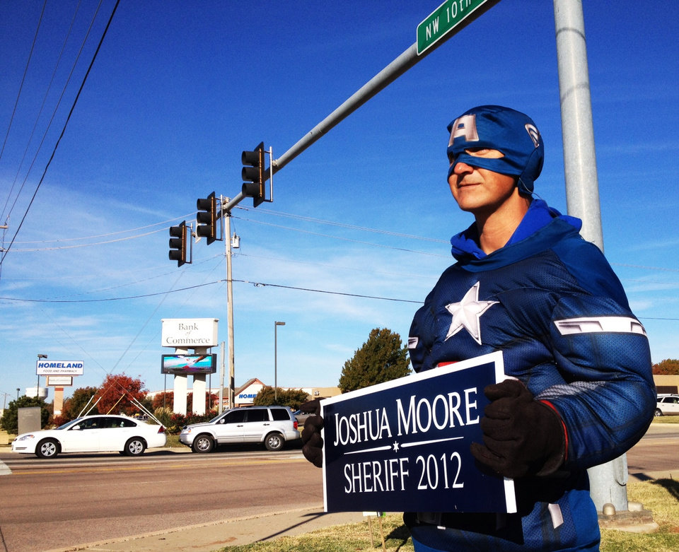 Tommy Reyes holds a campaign sign for Joshua Moore at NW 10th and Czech Hall Road in Yukon. Moore is running for Sheriff of Canadian County.