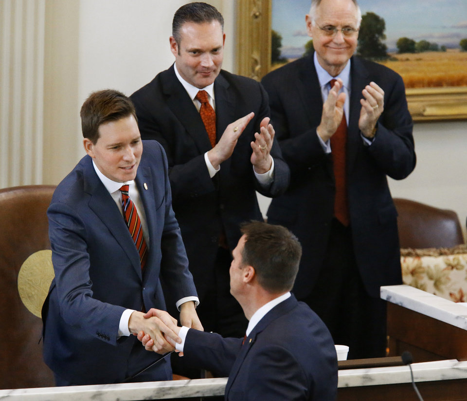 Photo - Gov. Kevin Stitt  shakes hands with Lt. Gov. Matt Pinnell, Speaker Charles McCall and Speaker Pro-Tempore Harold Wright after delivering his speech. said teachers deserve another pay raise and asked state lawmaker for the money to fund it in his first State-of-the-State address, which he also used to outline his vision for an economy-focused administration that will produce an efficient and adaptive state government. He outlined his plans moving forward in his first term as governor while speaking to lawmakers on Monday, Feb. 4, 2019, as the 57th Legislature officially began.  Photo by Jim Beckel, The Oklahoman.