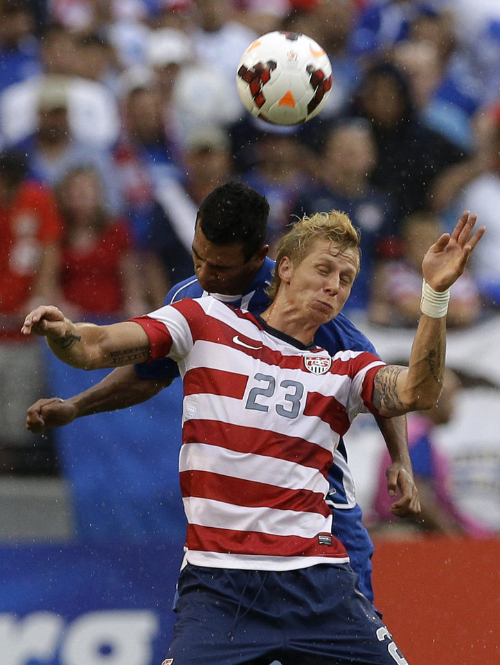 Photo - United States' Brek Shea (23) heads a ball in front of El Salvador's Xavier Garcia Orellana during the second half in the quarterfinals of the CONCACAF Gold Cup soccer tournament on Sunday, July 21, 2013, in Baltimore. The United States won 5-1. (AP Photo/Patrick Semansky)