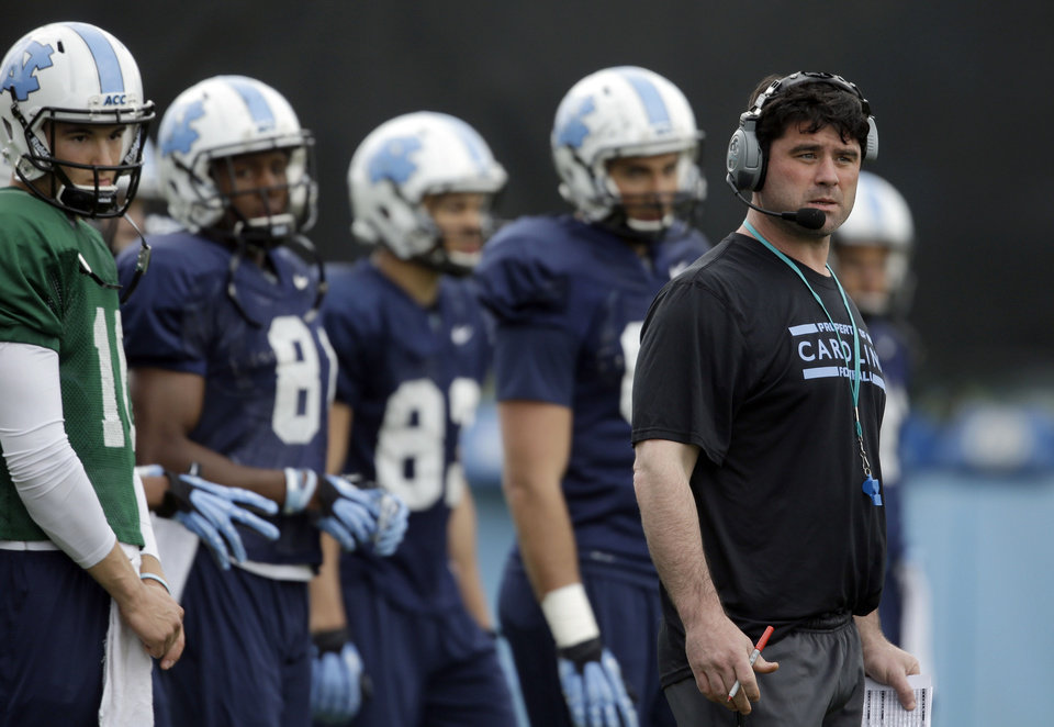 Photo - In this photo taken Wednesday, April 9, 2014 North Carolina assistant head coach for offense and tight ends Seth Littrell, right, watches a drill during an NCAA college football spring practice in Chapel Hill, N.C. After spending the last two seasons at Indiana, Littrell is preparing for his first season with the Tar Heels. (AP Photo/Gerry Broome)