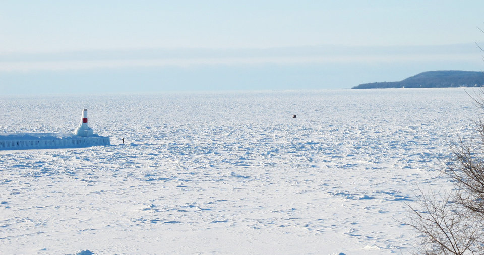 Photo - This Feb. 11, 2014 photo the pier and lighthouse  at Lake Michigan's Little Traverse Bay at Petoskey, Mich., is surrounded by thick ice. Nearly 88 percent of the Great Lakes' surface area has frozen over this winter, the most extensive ice-over in 20 years. (AP Photo/John Flesher)