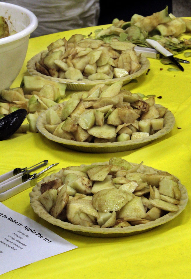 Seasoned apples are piled into crusts ready for baking at an Apple Pie 101 workshop at the Norman Public Library. PHOTO BY STEVE SISNEY, THE OKLAHOMAN <strong>STEVE SISNEY</strong>