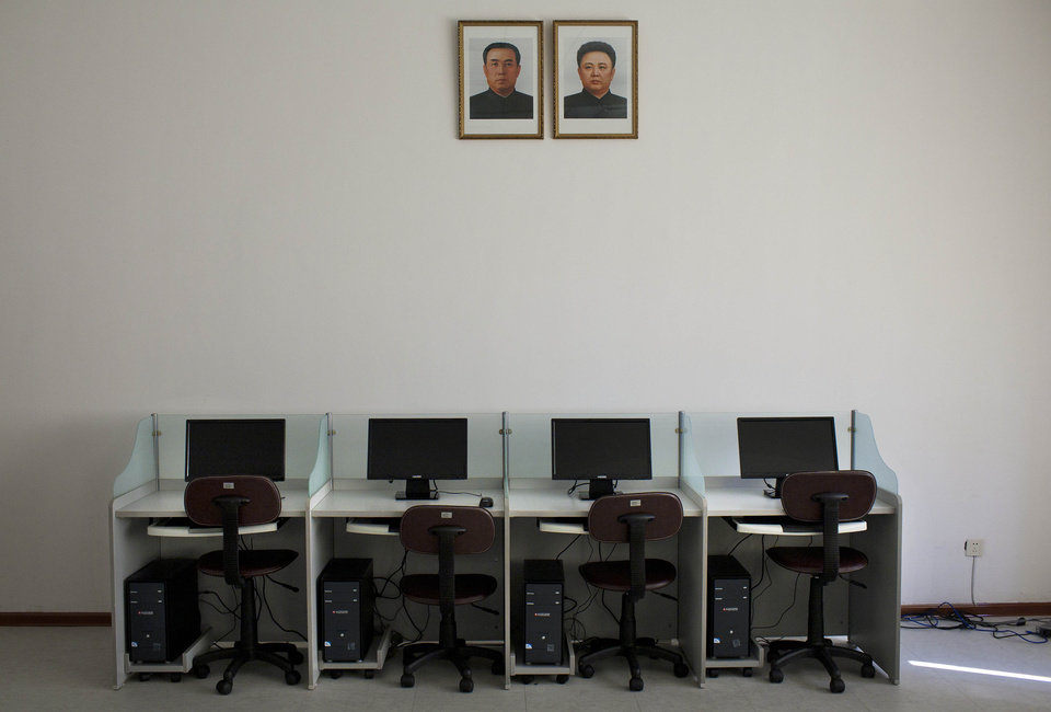 Photo - FILE - In this Oct. 5, 2011 file photo, portraits of North Korea's late leaders Kim Il Sung, left, and Kim Jong Il hang on a wall over a bank of computers at Pyongyang University of Science and Technology. North Korea is literally off the charts regarding Internet freedoms. There essentially aren't any. But the country is increasingly online. Though it deliberately and meticulously keeps its people isolated and in the dark about the outside world, it knows it must enter the information age to survive in the global economy. (AP Photo/David Guttenfelder, File)