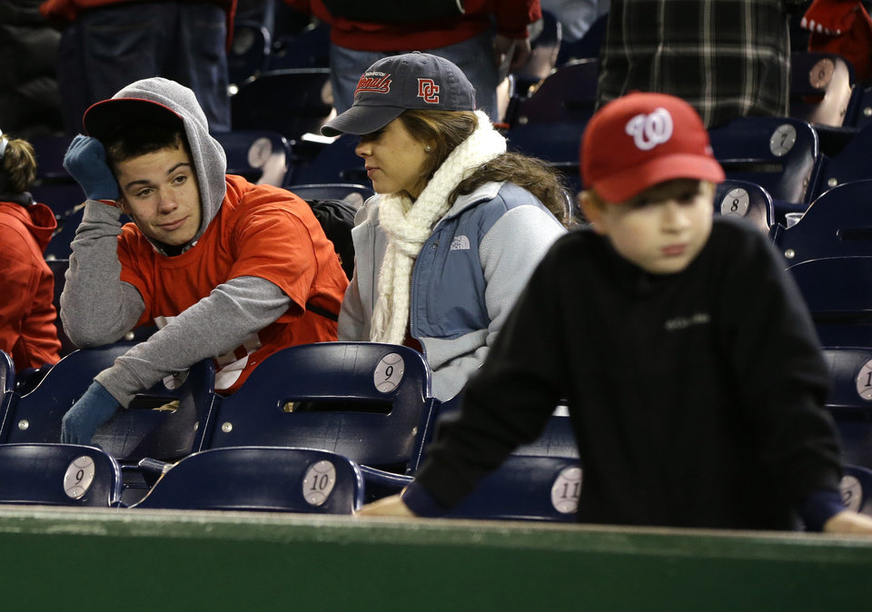 Washington Nationals fans look on after Game 5 of the National League division baseball series against the St. Louis Cardinals on Saturday, Oct 13, 2012, in Washington. St. Louis won 9-7. (AP Photo/Pablo Martinez Monsivais)