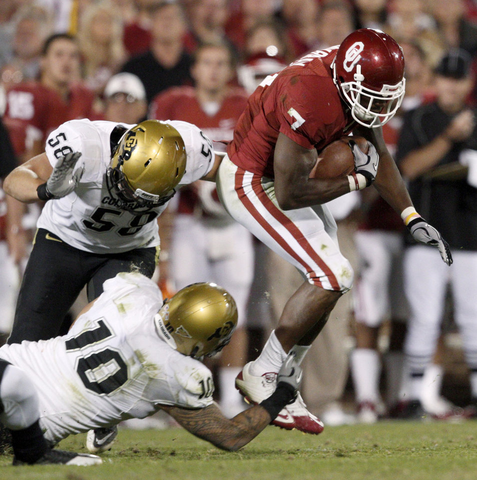 Photo - OU's DeMarco Murray runs past Colorado's Tyler Ahles, top, and Michael Sipili during the college football game between the University of Oklahoma (OU) Sooners and the University of Colorado Buffaloes at Gaylord Family-Oklahoma Memorial Stadium in Norman, Okla., Saturday, October 30, 2010. Photo by Bryan Terry, The Oklahoman