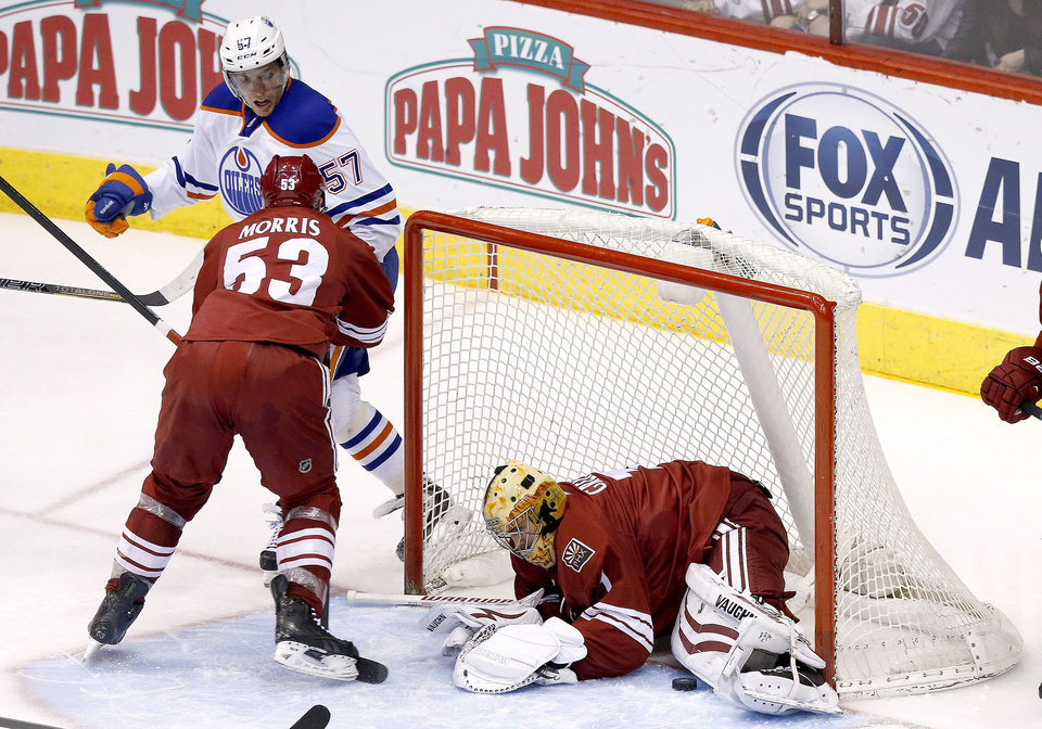 Photo - Phoenix Coyotes' Thomas Greiss, right, of Germany, makes a save on a shot by Edmonton Oilers' David Perron (57) as Coyotes' Derek Morris (53) defends during the second period of an NHL hockey game, Friday, April 4, 2014, in Glendale, Ariz. (AP Photo/Ross D. Franklin)