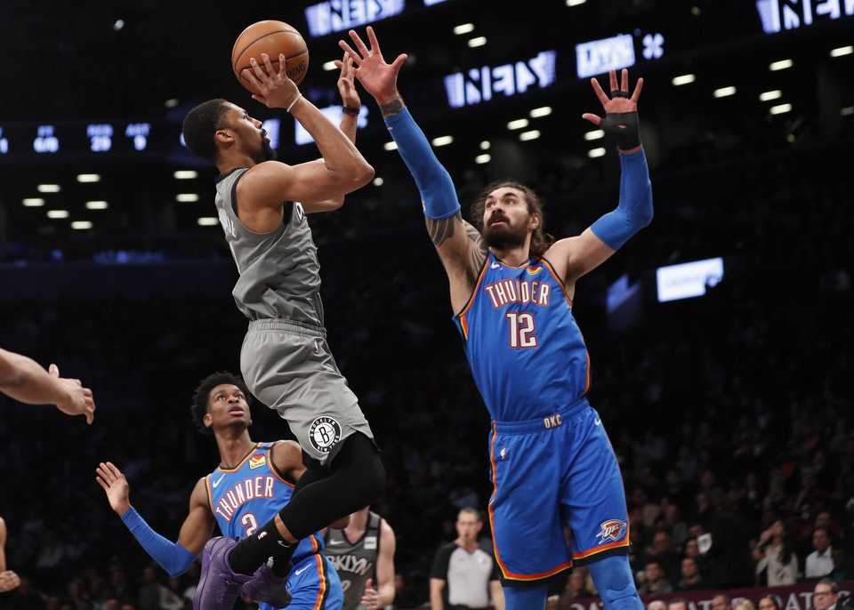 Photo - Oklahoma City Thunder center Steven Adams (12) defends and Thunder guard Shai Gilgeous-Alexander (2) watches as Brooklyn Nets guard Spencer Dinwiddie (8) goes up for a shot during the second half of an NBA basketball game, Tuesday, Jan. 7, 2020, in New York. The Thunder defeated the Nets 111-103 in overtime. (AP Photo/Kathy Willens)