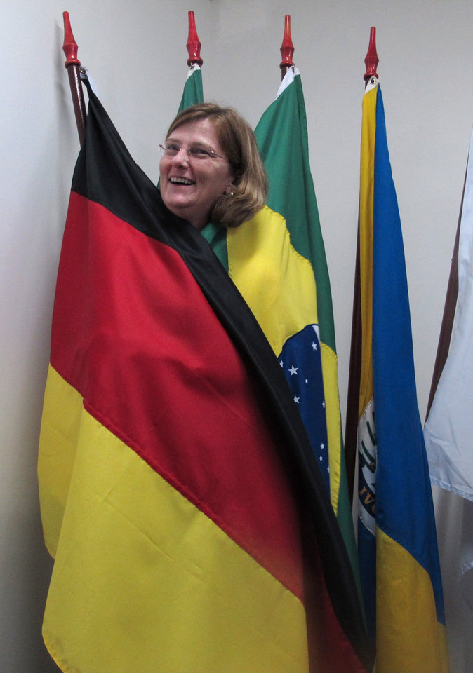 Photo - Government worker Margarida Utizig wraps herself in German and Brazilian flags inside a meeting room at the local government offices in Ivoti, Brazil, Friday, June 28, 2014. German-Brazilians in the region are supporting Germany and Brazil at the World Cup soccer tournament, but if and when the two sides meet, they say they'll support Brazil. (AP Photo/Chris Brummitt)