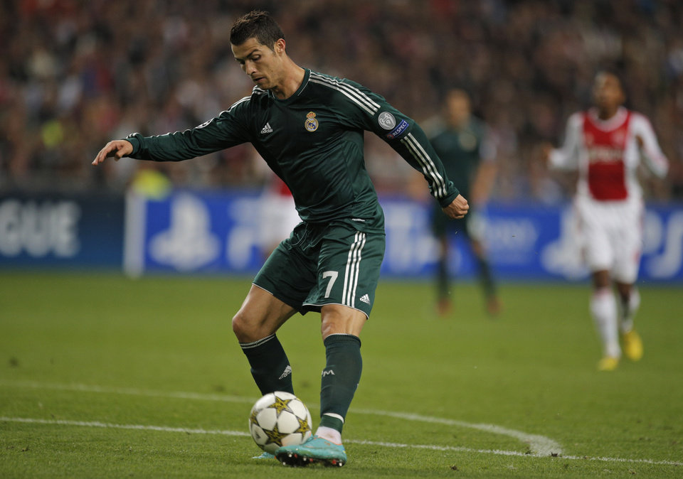 Photo -   Real Madrid player Cristiano Ronaldo tips the ball over Ajax goalkeeper Kenneth Vermeer, not seen, to score 4-1 during the Champions League Group D soccer match at ArenA stadium in Amsterdam, Netherlands, Wednesday Oct. 3, 2012. (AP Photo/Peter Dejong)