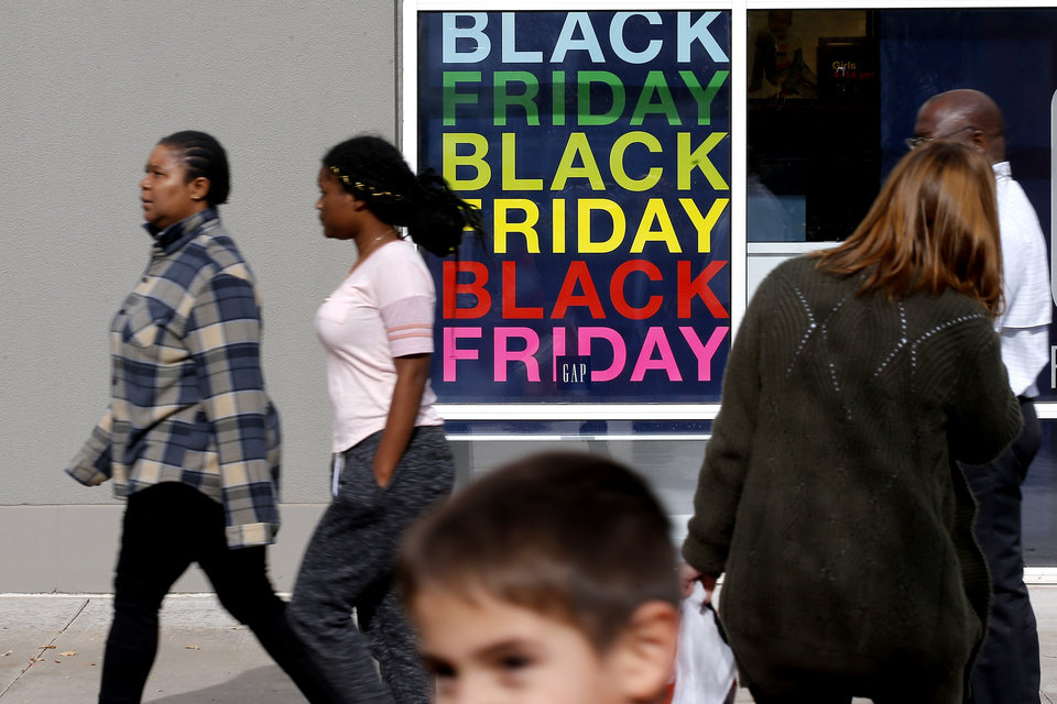 Photo -  Shoppers walk past a Black Friday shopping sign at the OKC Outlets in Oklahoma City on Wednesday. [Bryan Terry/The Oklahoman]
