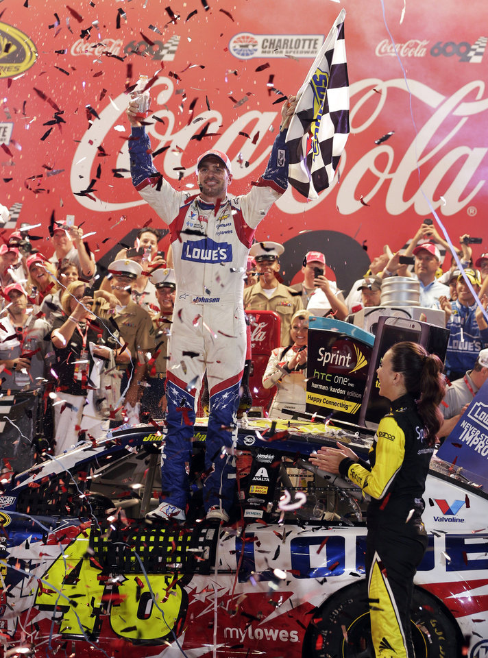 Photo - Driver Jimmie Johnson celebrates in Victory Lane after winning the NASCAR Sprint Cup series Coca-Cola 600 auto race at Charlotte Motor Speedway, Sunday, May 25, 2014, in Concord, N.C. (AP Photo/Chuck Burton)