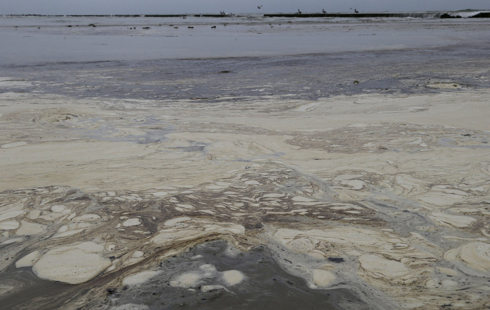 Photo - Oil sludge floats on the surface of the water on East Beach in Galveston, Texas, Monday, March 24, 2014. Thousands of gallons of tar-like oil spilled into the major U.S. shipping channel after a barge ran into a ship Saturday. (AP Photo/Pat Sullivan)