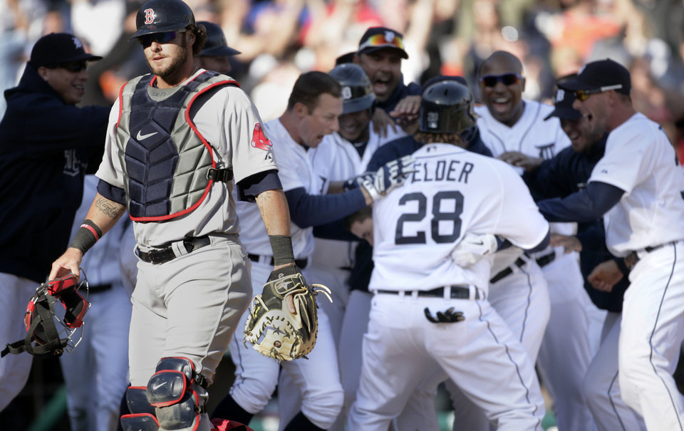 Photo -   Boston Red Sox catcher Jarrod Saltalamacchia, left, walks off the field as Detroit Tigers celebrate a 13-12 win in 11 innings, after a baseball game Sunday, April 8, 2012, in Detroit. (AP Photo/Duane Burleson)