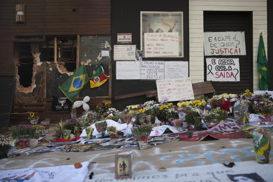 Photo - Posters, flowers, balloons and flags make up part of a makeshift memorial outside the Kiss nightclub in Santa Maria, Brazil, Wednesday, Jan. 30, 2013. A fast-moving fire roared through the crowded, windowless nightclub in this southern Brazilian city early Sunday, killing more than 230 people. Most of the dead were college students 18 to 21 years old, but they also included some minors. Almost all died from smoke inhalation rather than burns. The blaze was the deadliest in Brazil since at least 1961, when a fire that swept through a circus killed 503 people in Niteroi, Rio de Janeiro. (AP Photo/Felipe Dana)