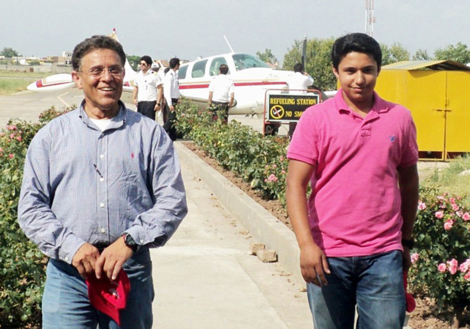 Photo - In this July 2014 photo provided by The Citizens Foundation 17-year-old Haris Suleman and his father Babar Suleman, 58, walk away from their single-engine airplane at a stop Islamabad, Pakistan, on their around-the-world flight. The body of the Plainfield, Indiana, teen was recovered after the plane crashed Tuesday, July 22, 2014 shortly after taking off from Pago Pago in American Samoa. Crews were still searching for Babar Suleman. (AP Photo/Courtesy The Citizens Foundation)