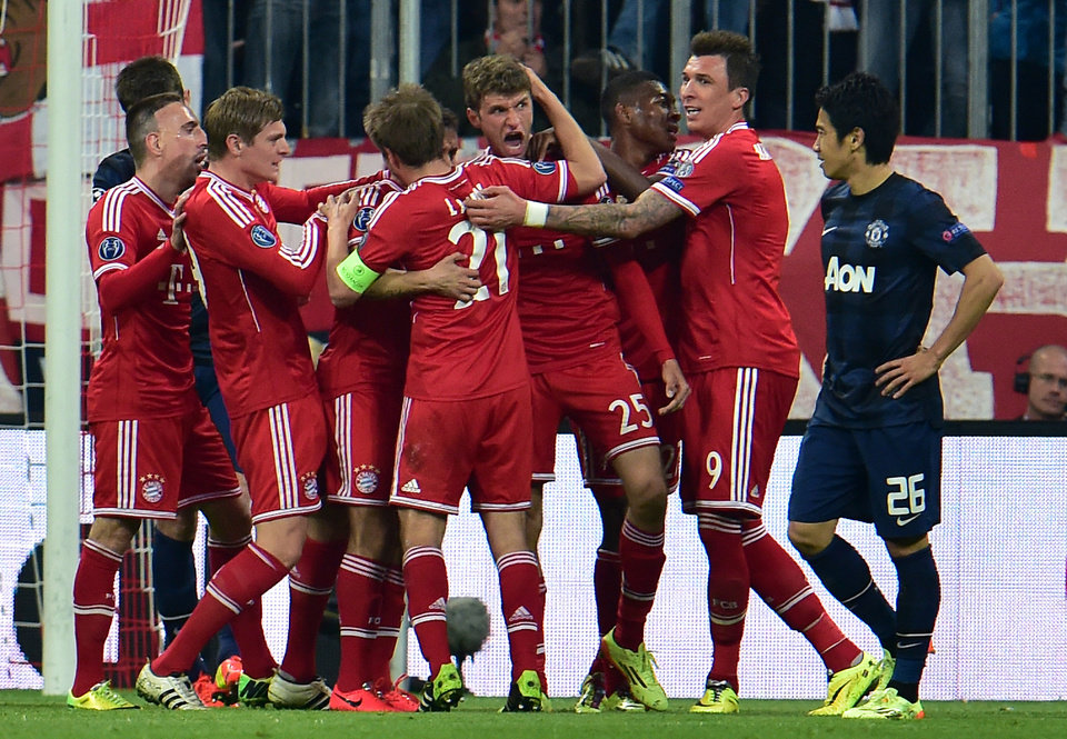 Photo - Bayern's scorer Thomas Mueller, center, and his teammates celebrate their side's 2nd goal during the Champions League quarterfinal second leg soccer match between Bayern Munich and Manchester United in the Allianz Arena in Munich, Germany, Wednesday, April 9, 2014. (AP Photo/Kerstin Joensson)