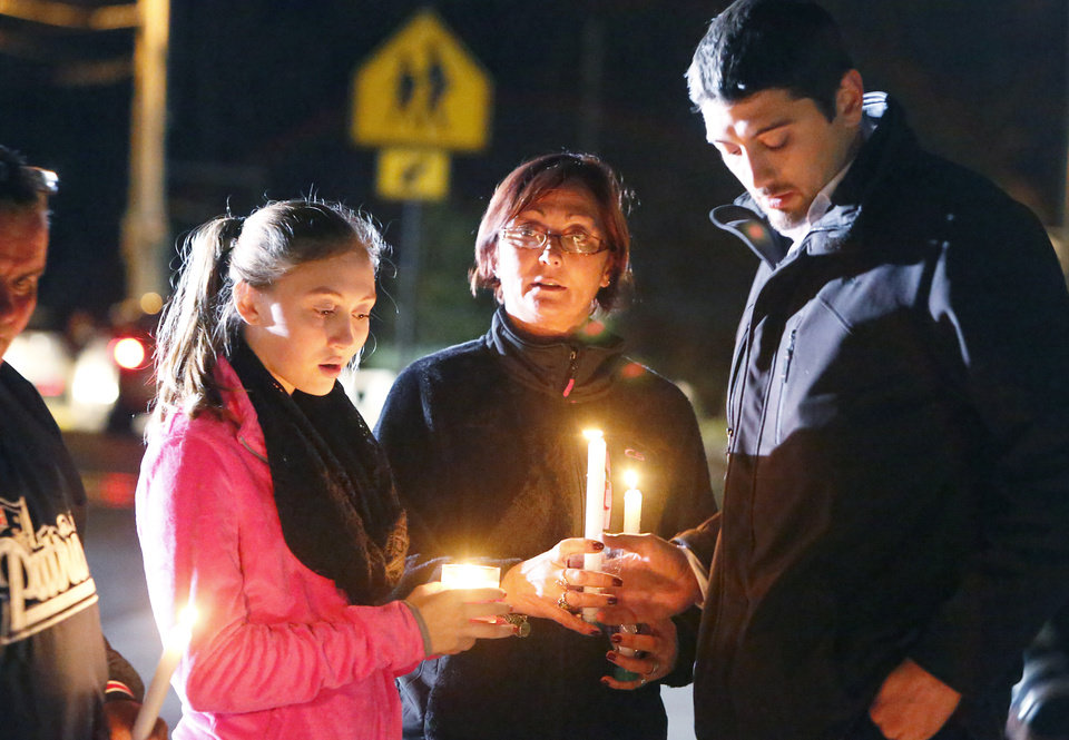 Photo - Parents and Danvers High School students hold candlelight vigil to mourn the death of Colleen Ritzer, a 24-year-old math teacher at Danvers High School, on Wednesday, Oct 23, 2013, in Danvers, Mass. Ritzer's body was found in woods behind the school, and Danvers High School student Philip Chism, 14, who was found walking along a state highway overnight, was charged with killing her. (AP Photo/ Bizuayehu Tesfaye)