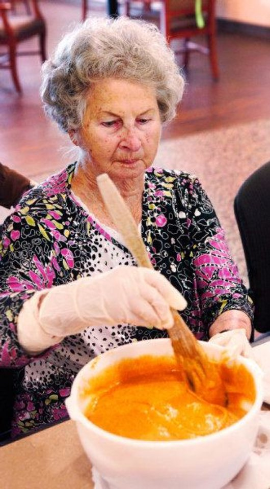 Photo - Betty Jones makes pumpkin bread as part of her cognitive stimulation therapy at Touchmark Coffee Creek.  JIM BECKEL - THE OKLAHOMAN